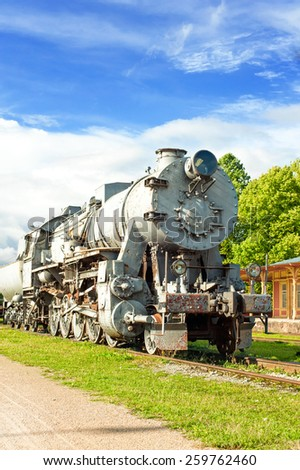 Old rustic steam locomotive on station platform. Cloudy sky background. Summertime outdoors.