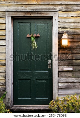 Old rustic vintage dilapidated antique house home building structure with green intricate front door and window with shutters closed and porch light lantern glowing turned on - stock photo