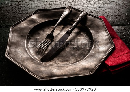 Old rustic vintage octagonal pewter plate with eating utensils and a bright red napkin on a dark textured cracked wood background, close up high angle view - stock photo