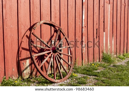 Old rustic wagon wheel beside a red barn. - stock photo