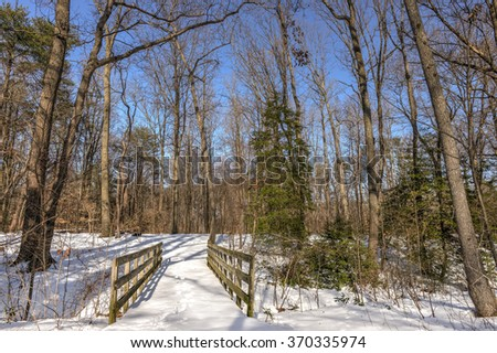 Old rustic walking bridge over a frozen stream in the Maryland woods covered in snow during Winter - stock photo