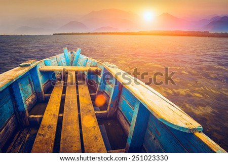 Old rustic wooden boat floating on a river to the sunset - stock photo