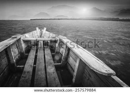 Old rustic wooden boat floating on a river to the sunset. Monochrome colors