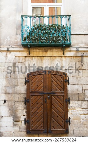Old rustic wooden gate on stone wall. - stock photo