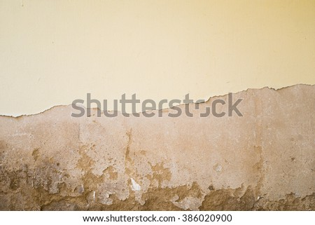 Old rustic yellow wall with peeled of paints.  Some cement is broken due to weathered deterioration - stock photo