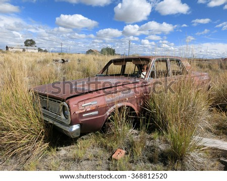 Old rusty abandoned car being overtaken by weeds - landscape photos - stock photo