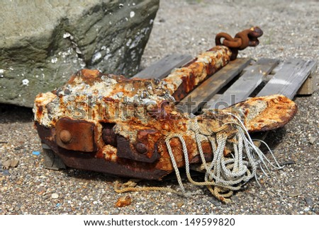 Old rusty anchor and rope. - stock photo