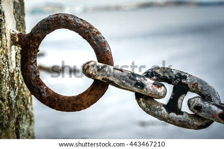 Old rusty anchor iron ship chain in sea port. Old fence made of obsolete boat chain elements with sea ocean in background. - stock photo