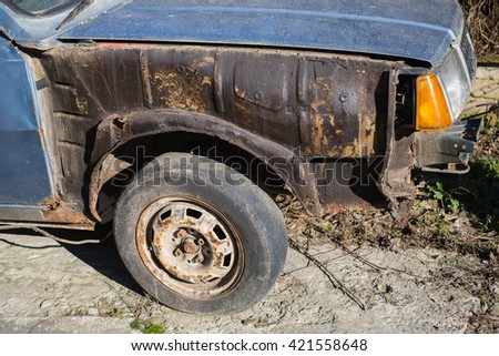 old rusty car, old wheel, old metal texture old crumpled cars, worn tire  - stock photo