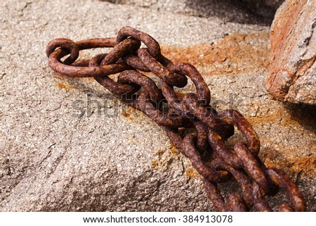Old rusty chain stapled stone wall - stock photo
