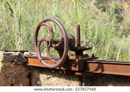 Old rusty crank handle in a dam - stock photo