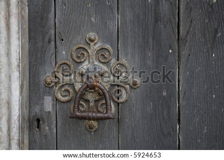 old rusty door knocker and handle on a cathedral door