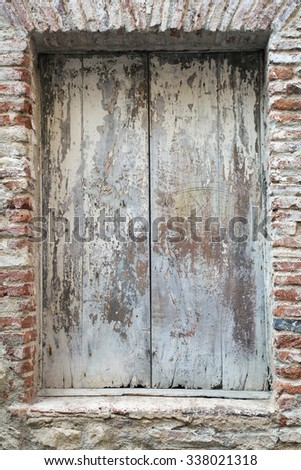 Old rusty gate in the mediterrian style house as a background texture. Front view. Vertical. Have a place for text.