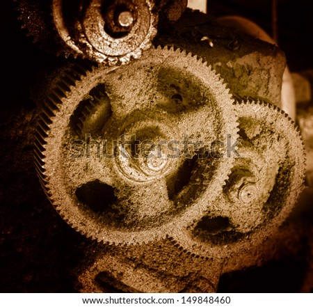 Old rusty gears, machinery parts at old metal factory - stock photo