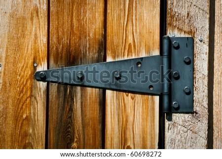 old rusty hinge on wooden door - stock photo