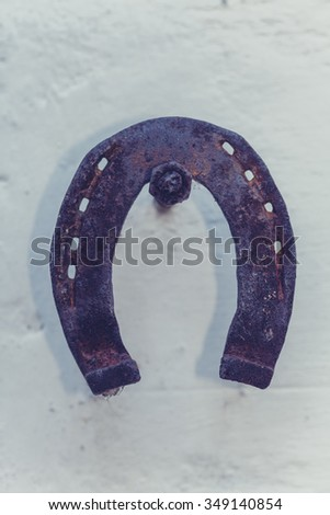 Old rusty horseshoe hanging on the wall - stock photo