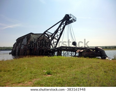 Old rusty industrial dredging ship beached on shore - landscape color photo - stock photo