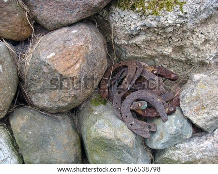 Old rusty iron horseshoes outdoor on stone wall close up.                                - stock photo