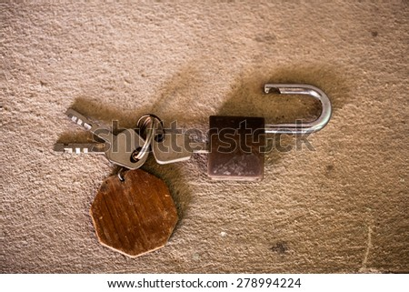 old rusty iron keys on cement background. - stock photo