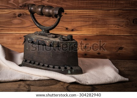 Old rusty iron on white cloth and wooden floor - stock photo