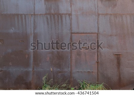 Old rusty iron wall with the door closed. - stock photo