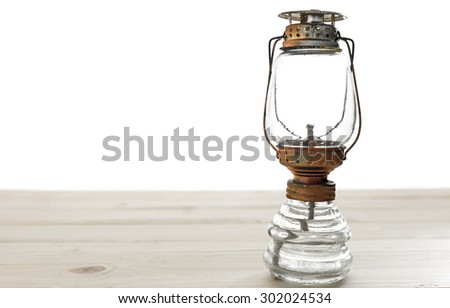 old rusty kerosene lamp,kerosene lamp on wooden table - stock photo