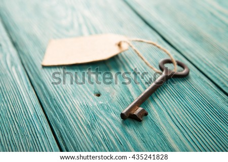 Old rusty key with a paper label on the wooden board - stock photo