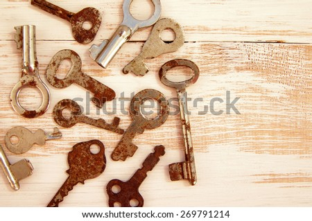 Old rusty keys to the locks on the wooden background. Collection of old lock keys - stock photo