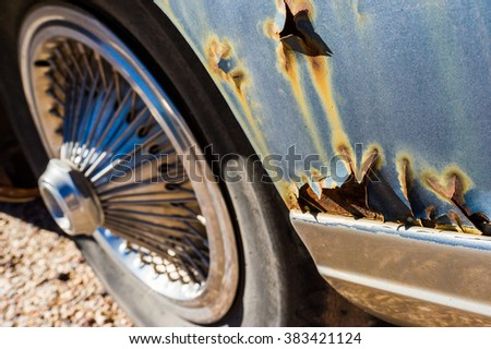 old rusty leaky vintage car close up details with chrome hubcaps