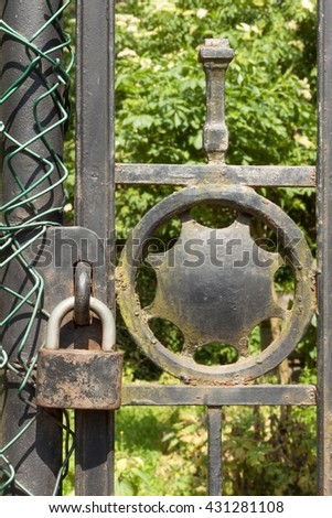 Old rusty lock on a metal gate into the garden. Lock on the iron gate. Symbol imprisonment and slavery. Property security chain. Closed iron gate with a lock. Safe lock.  - stock photo