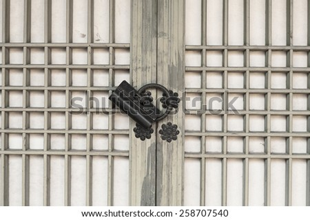 Old rusty lock on the wooden gate, Korea tradition style. - stock photo