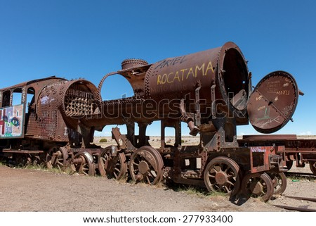 Old rusty locomotive with open steam boiler.Uyuni, train cemetery, Bolivia. Blue sky background - stock photo
