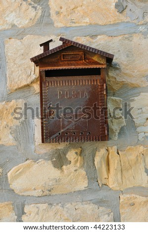 Old rusty mailbox on the stone wall of the rural home - stock photo