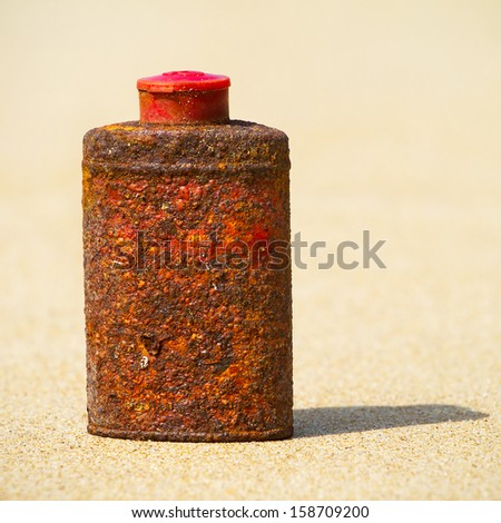 Old rusty metal bottle on the beach - stock photo