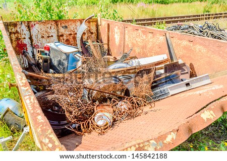 Old rusty metal container full of junk. - stock photo