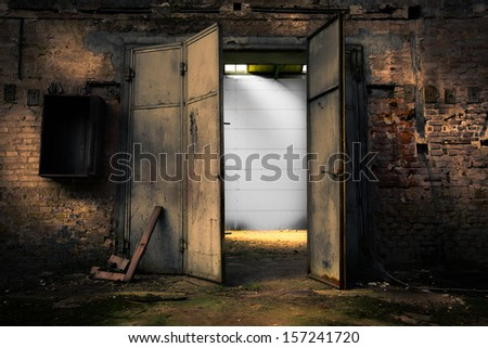 Old rusty metal door in an abandoned warehouse - stock photo