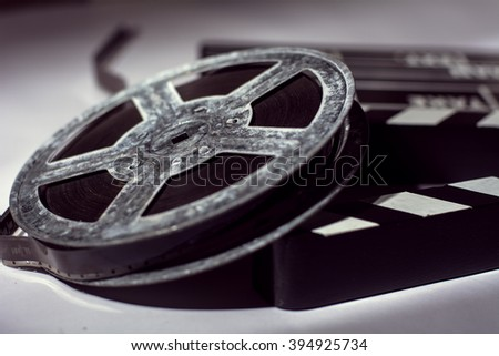Old rusty metal reel of film and cinema clap. - stock photo