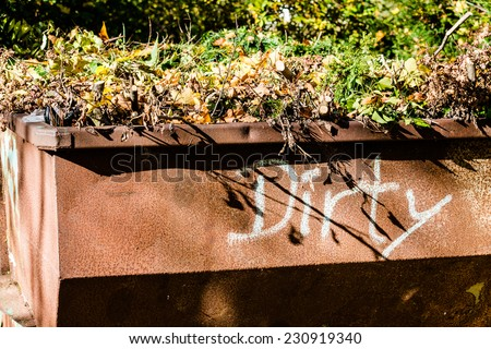 Old rusty metal waste container with green garden waste and word dirty painted on it - stock photo