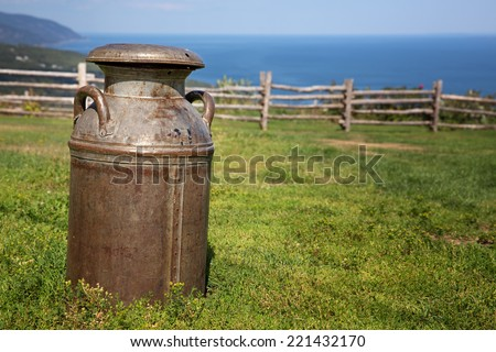 Old rusty milk churn in a field, with rustic wood fence and the sea in the background.  - stock photo