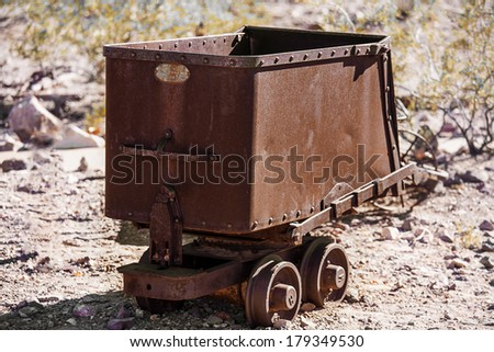 Old rusty mining ore cart in the desert - stock photo