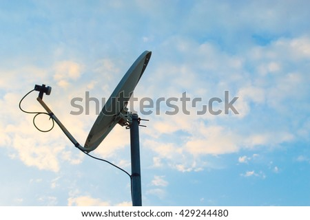 Old rusty old white satellite dishes through use  on sky background - stock photo