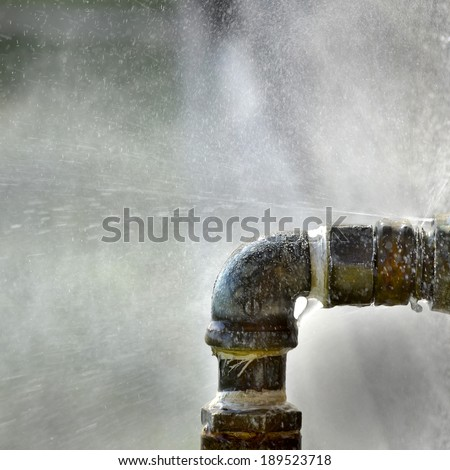 Old rusty pipe with leak and water spraying out - stock photo