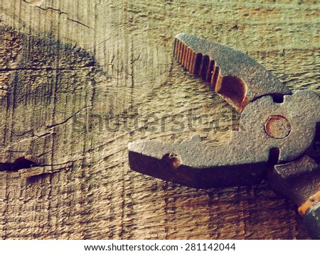 Old rusty pliers on old wooden table background. Old style photo - stock photo