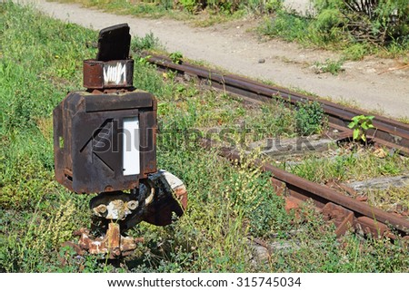 Old rusty railway switch next to an abandoned railway line