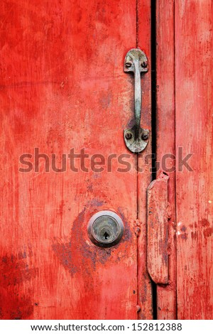 Old rusty red door.And brass lock. - stock photo