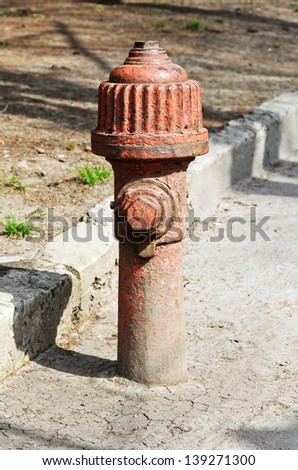 Old, rusty red fire hydrant on the street - stock photo