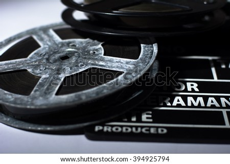 Old rusty roll of film and cinema clap. Toned image - stock photo
