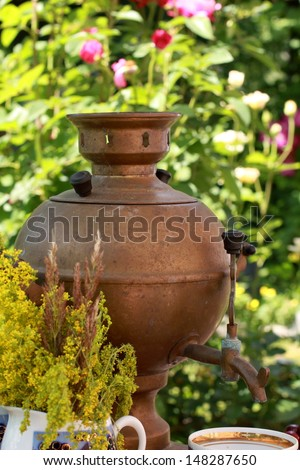 Old rusty samovar tea and ceramic dinner service in the summer garden/Antique Russian samovar - stock photo