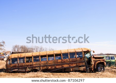 Old rusty school bus partly collapsed in salvage yard - stock photo