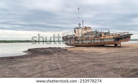Old rusty ship on sand beach agains river panorama at dawn. Solvychegodsk, Arkhangelsky region, Russia.